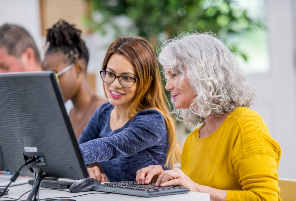 A group of women are working on computers. They are in a technology lab at a university. A Caucasian senior lady is getting help from another woman.